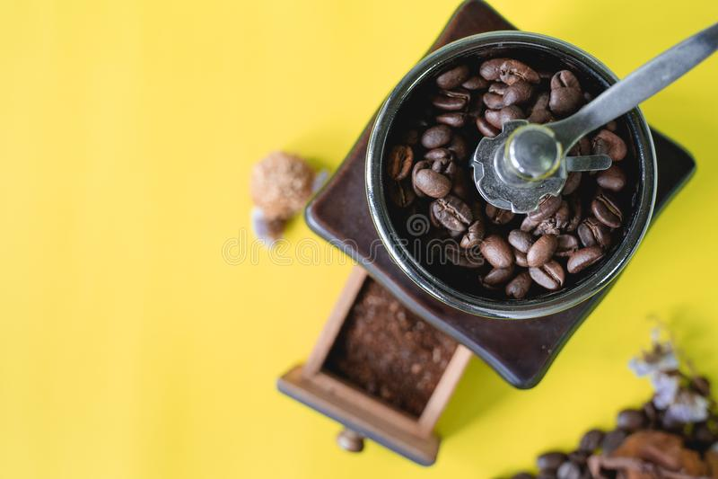 Feche acima dos feijões de café seletivos e do feijão de café sorrido no moedor de café de madeira do vintage no fundo amarelo fotografia de stock royalty free