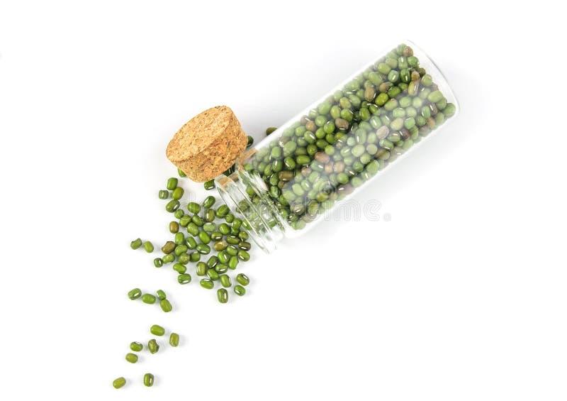 Feche acima dos feijões de mung verdes na garrafa de vidro no fundo branco fotos de stock royalty free