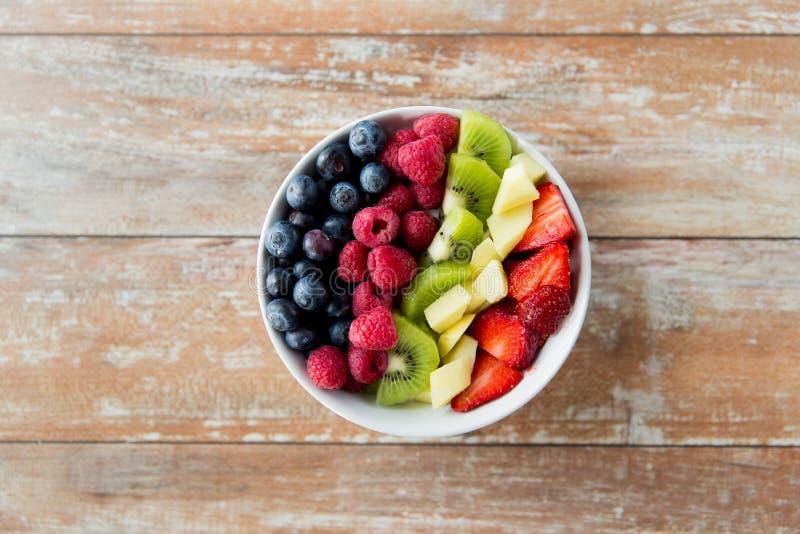 Feche acima dos frutos e das bagas na bacia na tabela fotografia de stock