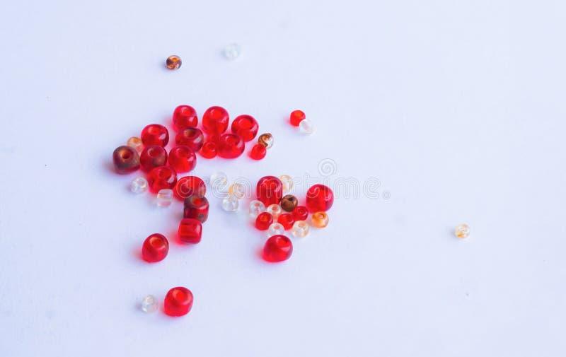 Feche acima dos grânulos vermelhos e brancos isolados foto de stock royalty free