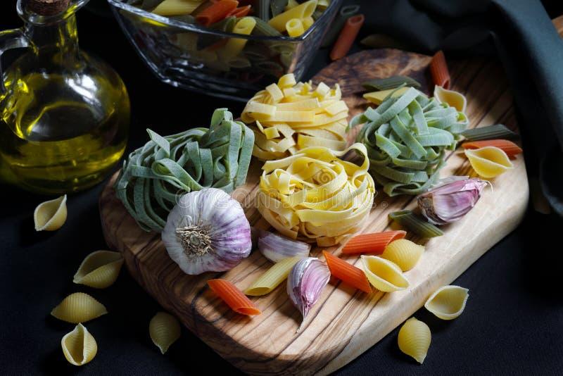Feche acima dos ingredientes escuros da massa do alimento do claro-escuro com tagliatelle fotos de stock