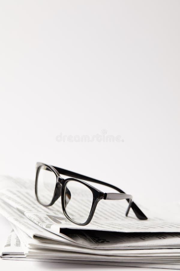 feche acima dos jornais com monóculos pretos, no branco com espaço da cópia fotografia de stock