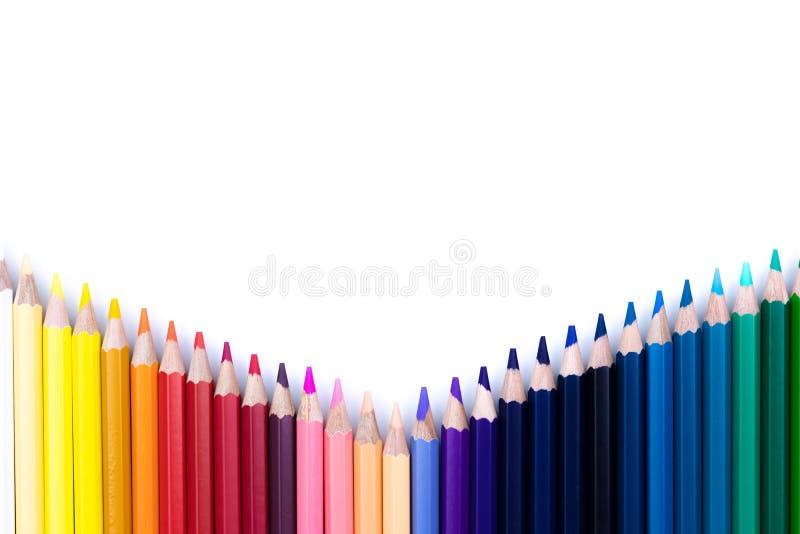 Feche acima dos lápis coloridos sem emenda enfileiram com a onda em um mais baixo lado isolado no fundo branco imagem de stock