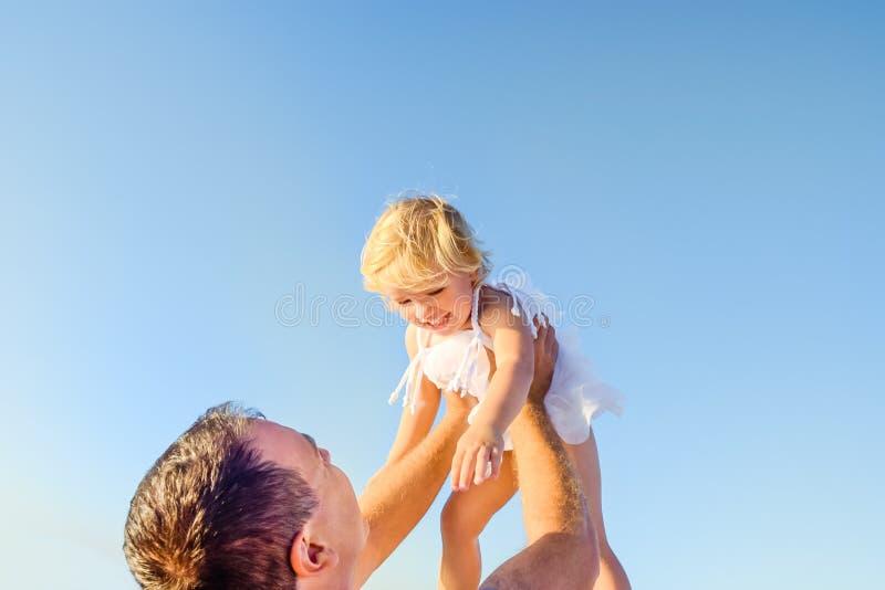 Feche acima dos lances do pai sua filha acima da elevação contra si mesmo no fundo do céu azul Família feliz do tempo Foco seleti imagens de stock