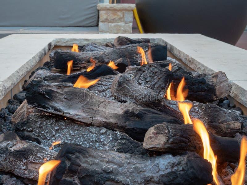 Feche acima dos logs que queimam-se em um grande, poço branco, de pedra do fogo imagem de stock royalty free