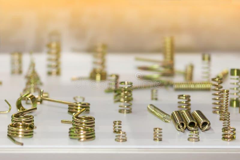 Feche acima dos muitos a cor dourada brilhante amável da mola de bobina do metal da flexibilidade para industrial na tabela imagem de stock