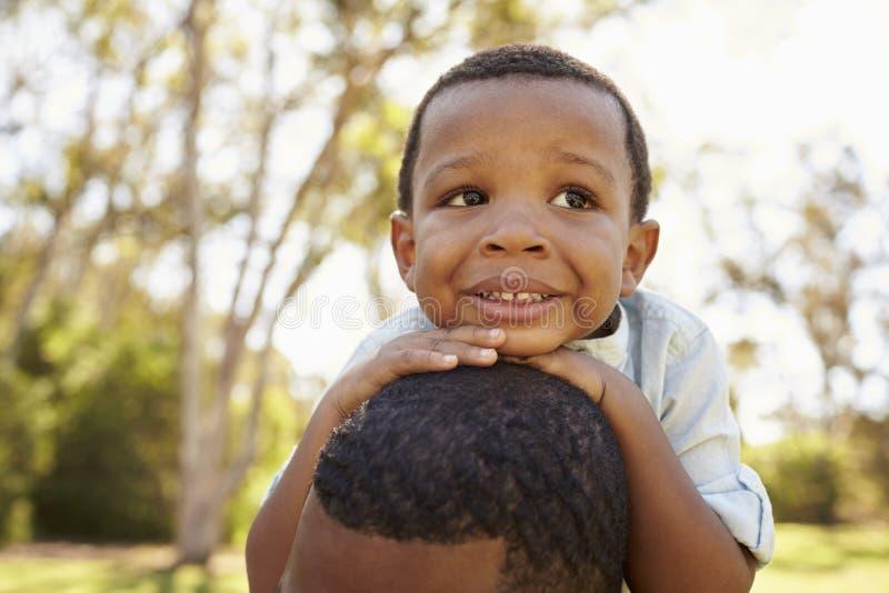 Feche acima dos ombros de Carrying Son On do pai que andam no parque imagens de stock royalty free
