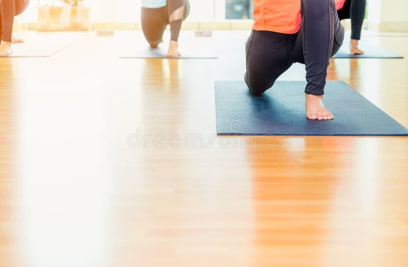 Feche acima dos pés da classe da ioga que esticam na esteira no classroo do estúdio fotografia de stock