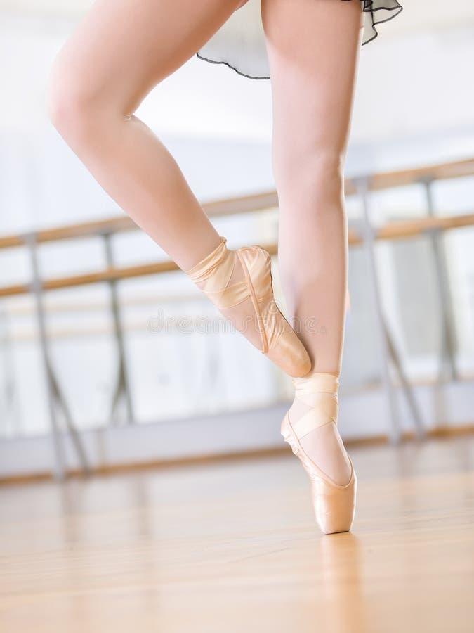 Feche acima dos pés da dança da bailarina nos pointes imagem de stock