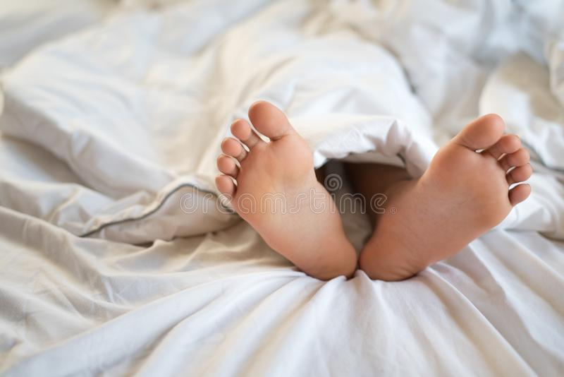 Feche acima dos pés da jovem criança que dormem na cama fotografia de stock royalty free