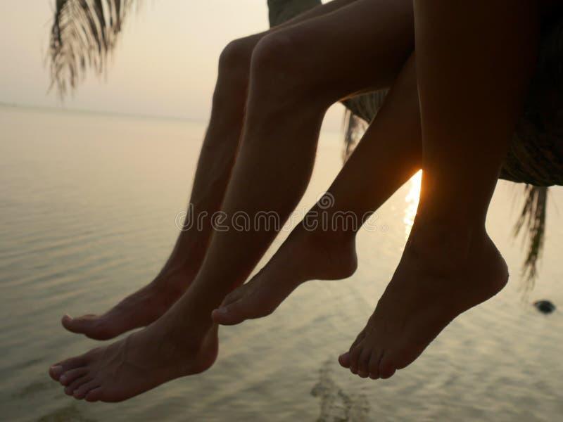 Feche acima dos pés de um par que senta-se em uma palmeira durante o por do sol no litoral imagens de stock