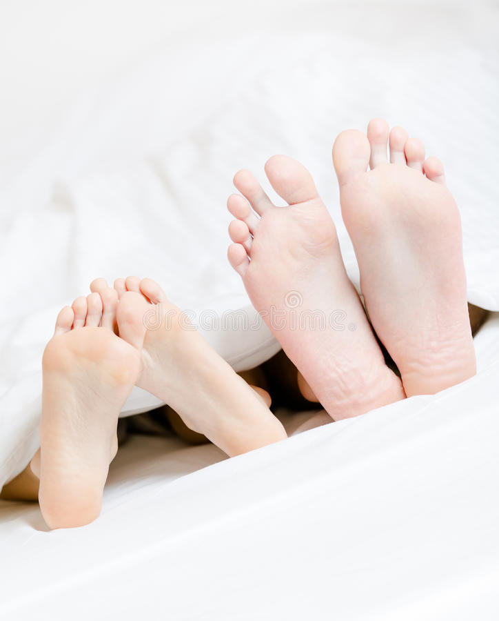 Feche acima dos pés dos pares que encontram-se na cama fotos de stock royalty free