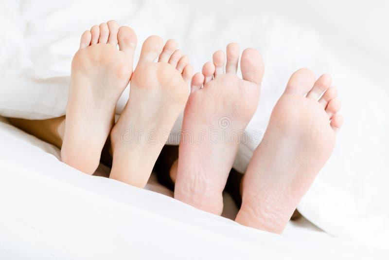 Feche acima dos pés dos pares que encontram-se no quarto imagem de stock royalty free