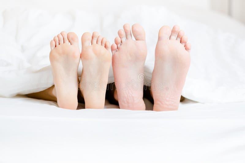 Feche acima dos pés dos pares que encontram-se no quarto fotografia de stock royalty free