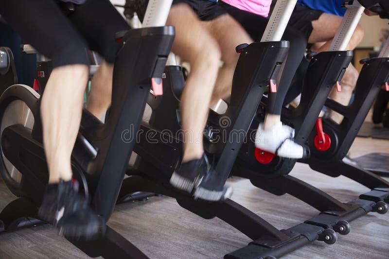 Feche acima dos pés em bicicletas de exercício na classe de gerencio do Gym imagens de stock royalty free