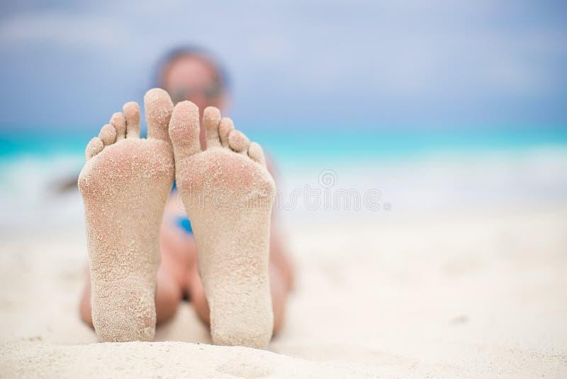Feche acima dos pés fêmeas no Sandy Beach branco fotografia de stock