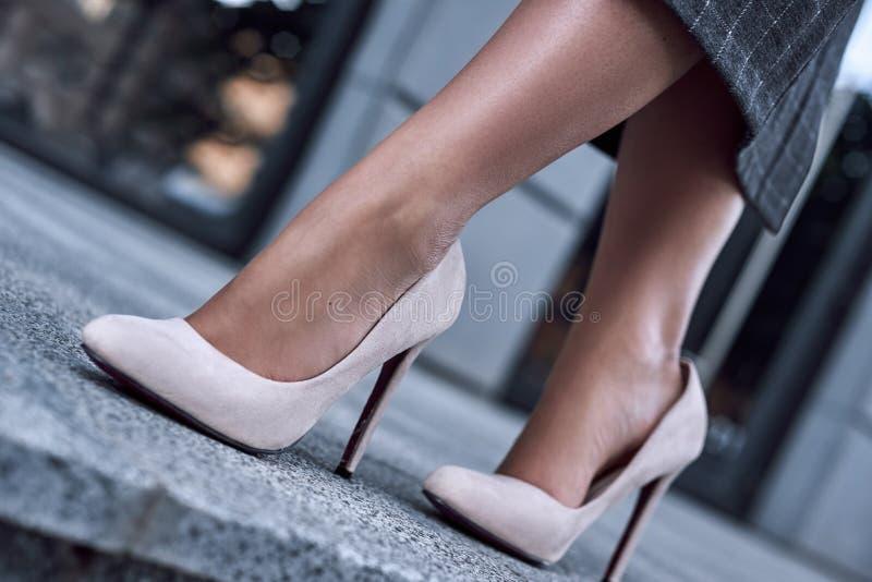 Feche acima dos pés magros de sapatas vestindo do salto alto da mulher foto de stock