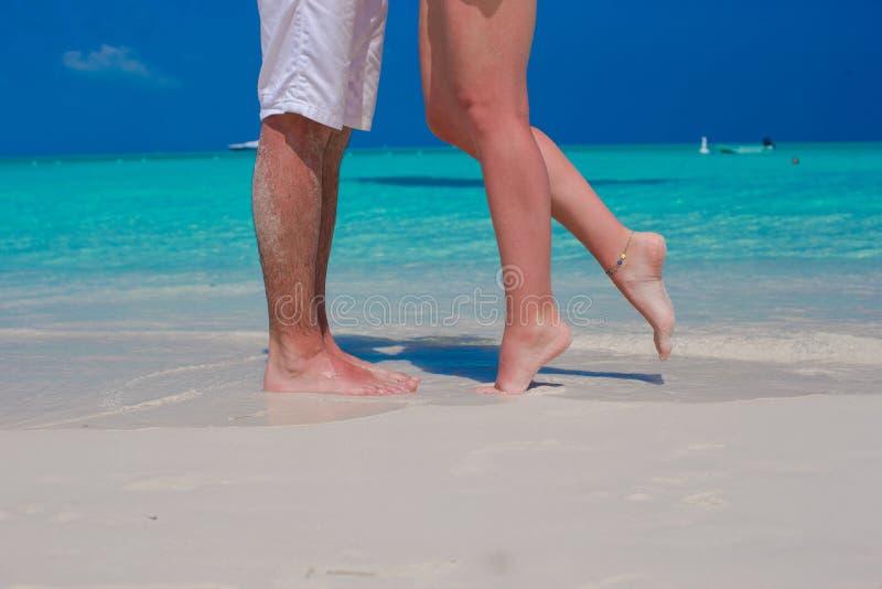 Feche acima dos pés masculinos e fêmeas na areia branca imagem de stock