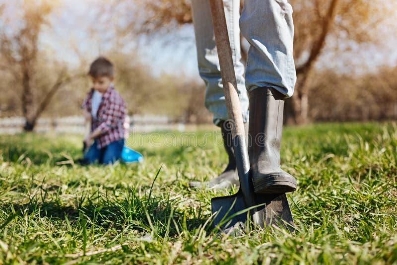 Feche acima dos pés nas botas de borracha no jardim imagem de stock