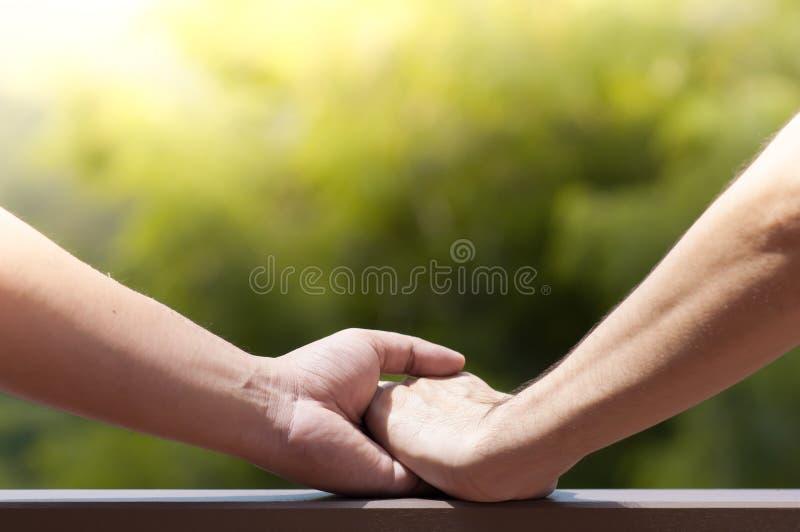 Feche acima dos pares alegres dos homens que guardam as mãos no backgr natural verde foto de stock royalty free