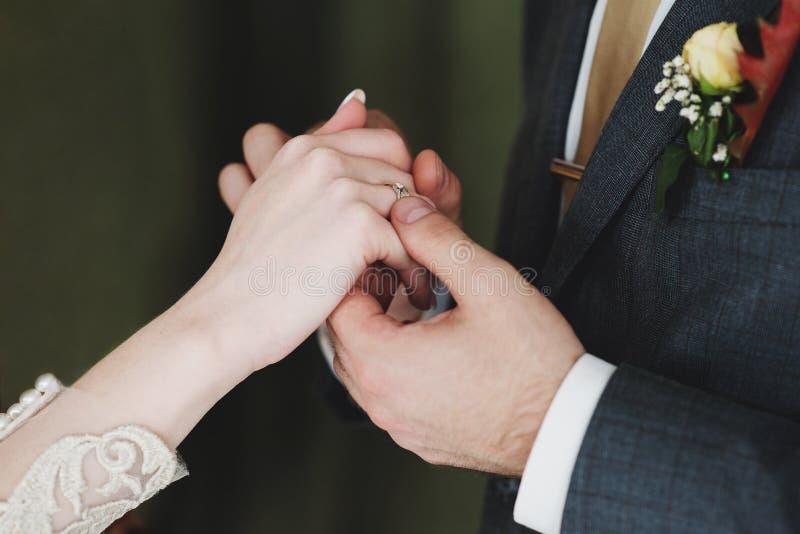 Feche acima dos pares contratados que guardam as mãos com aliança de casamento fotografia de stock