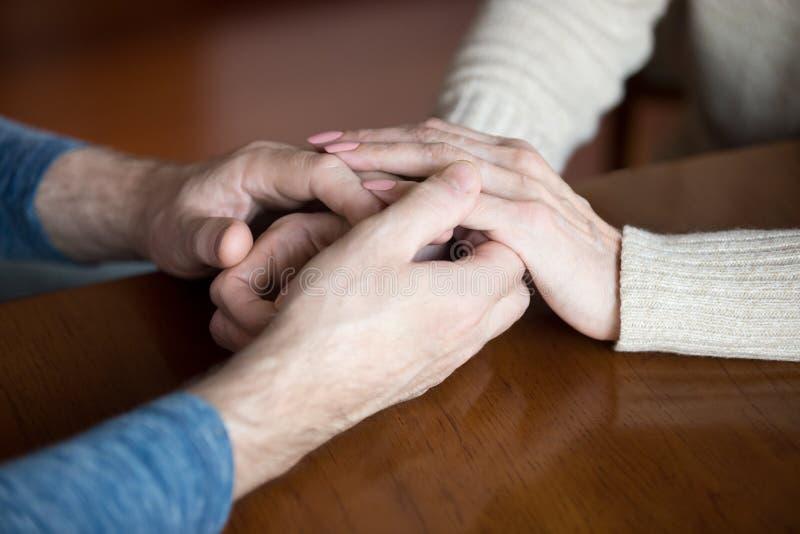 Feche acima dos pares da pessoa idosa que guardam as mãos que dão o apoio fotografia de stock royalty free