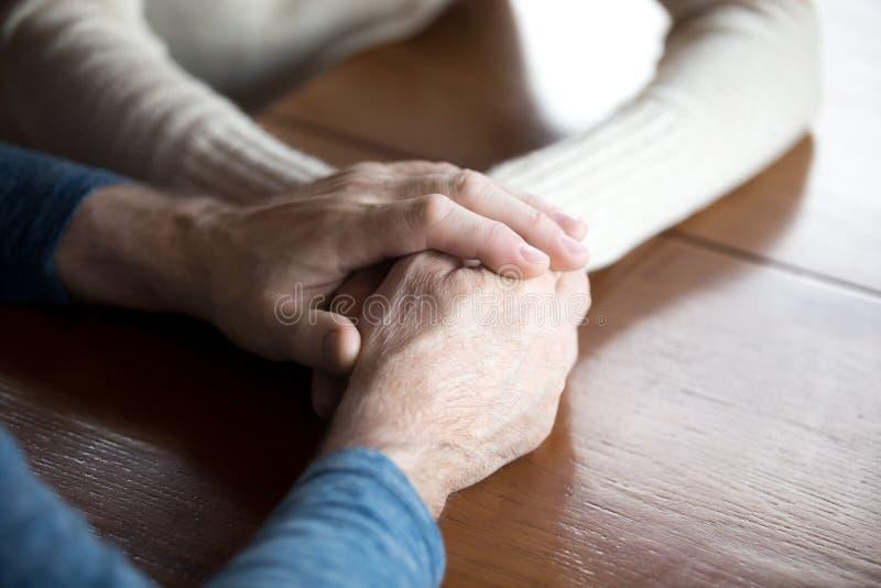 Feche acima dos pares envelhecidos que guardam as mãos que expressam o cuidado eterno imagens de stock