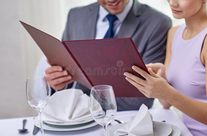 Feche acima dos pares felizes com menu no restaurante fotos de stock royalty free