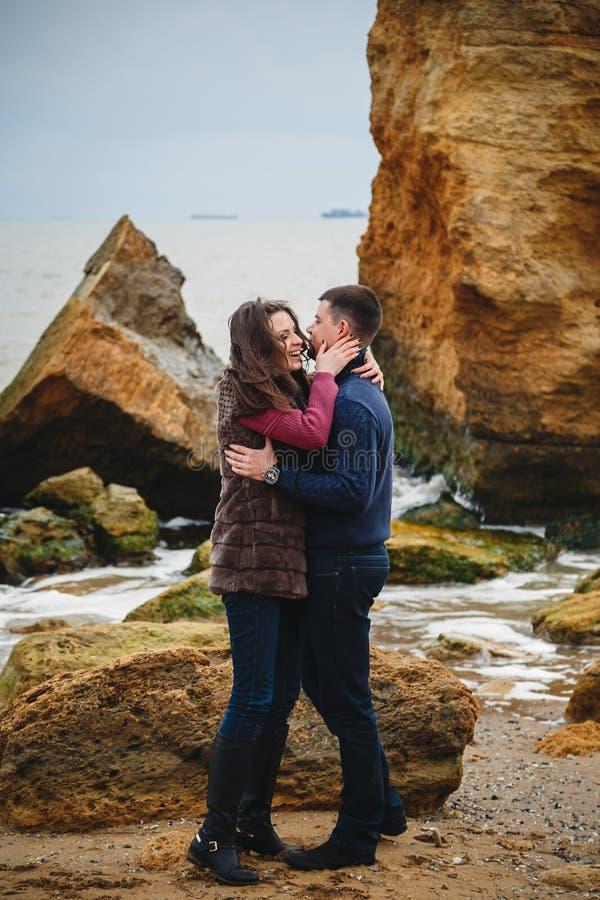 Feche acima dos pares novos atrativos românticos que abraçam na costa fotos de stock
