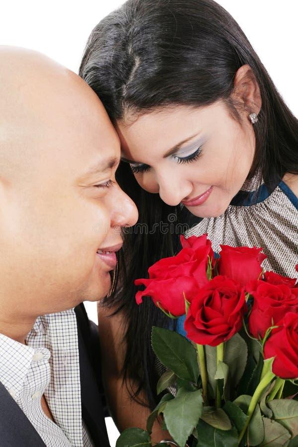 Feche acima dos pares que guardam um ramalhete de rosas vermelhas imagem de stock