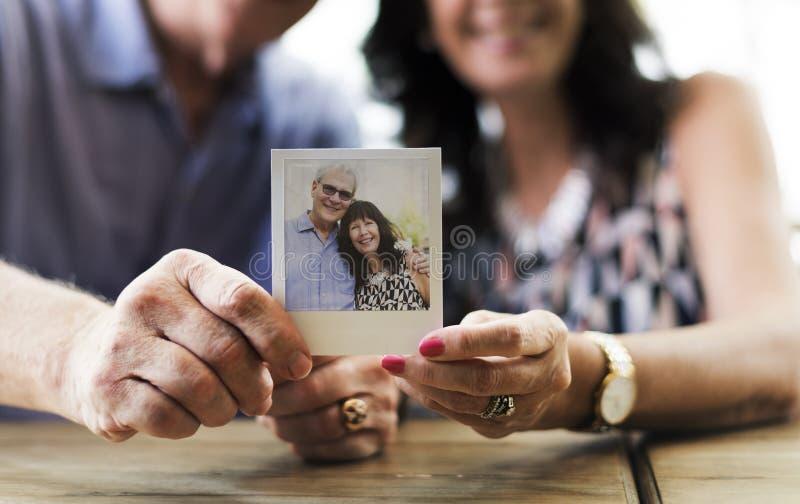 Feche acima dos pares que mostram a imagem da câmera instantânea fotos de stock royalty free