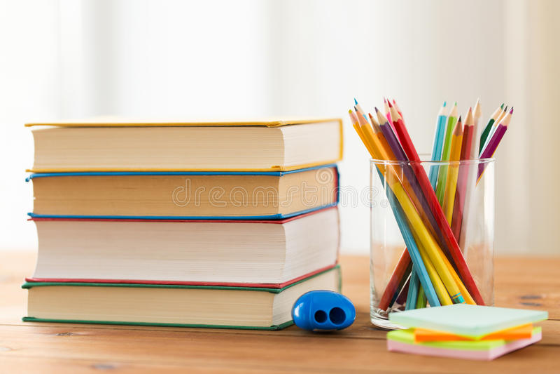 Feche acima dos pastéis ou os lápis e os livros da cor imagem de stock royalty free