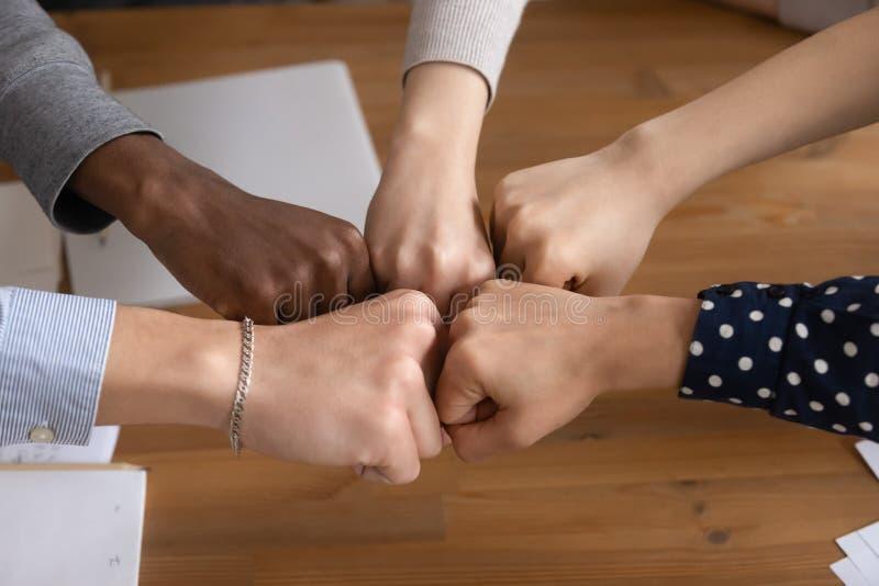 Feche acima dos povos diversos juntam-se às mãos que mostram a unidade foto de stock