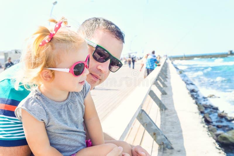 Feche acima dos retratos do pai e da filha pequena nos óculos de sol que olham ao mar na frente marítima de Tel Aviv no dia ensol fotografia de stock