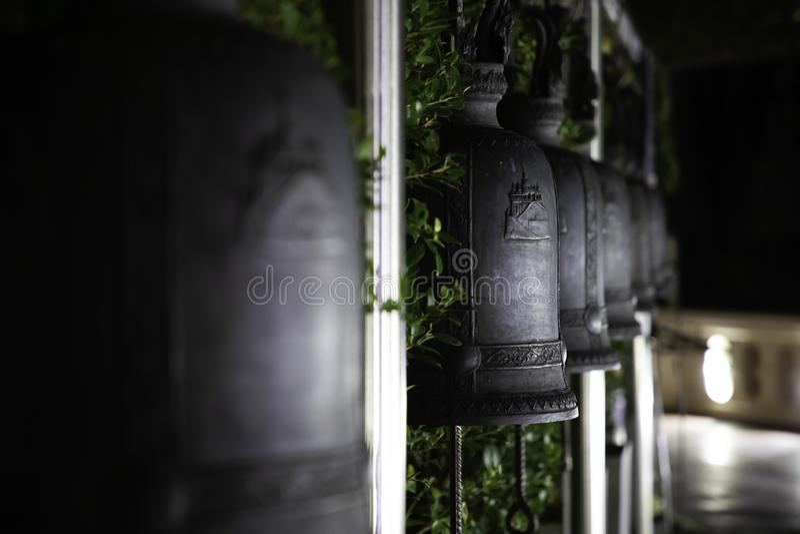 Feche acima dos sinos alinhados do ferro em um templo tailandês na noite fotos de stock