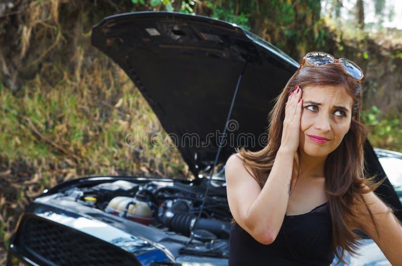 Feche acima dos sunglases vestindo preocupados da mulher em seus cabeça, t-shirt preto e calças de brim, tendo um problema com o  fotografia de stock