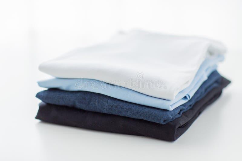 Feche acima dos t-shirt passados e dobrados na tabela foto de stock