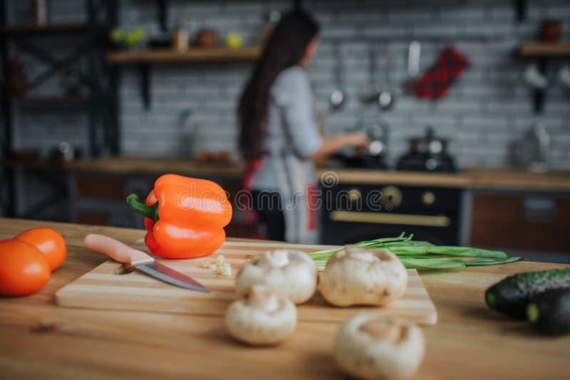 Feche acima dos vegetais e da faca na tabela da mesa na cozinha Suporte da mulher no fogão e no cozinheiro Olha ocupada foto de stock