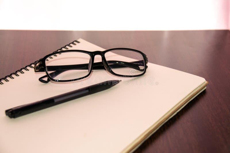 Feche acima dos vidros e da pena no caderno na tabela imagem de stock