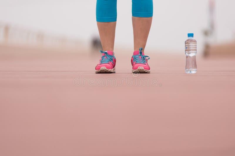 Feche acima em tênis de corrida e em garrafa da água fotografia de stock