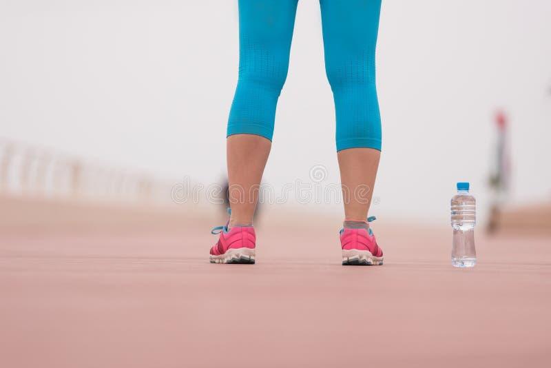 Feche acima em tênis de corrida e em garrafa da água imagem de stock