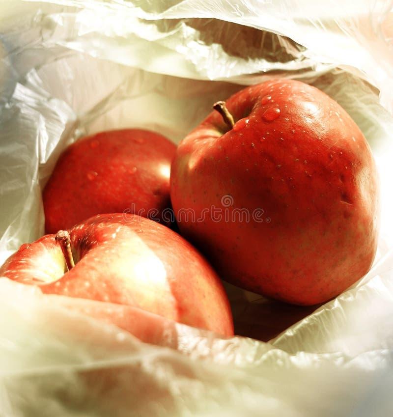 Feche acima em três maçãs vermelhas que encontram-se em um saco de plástico fino transparente fotografia de stock royalty free