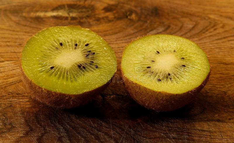 Feche acima em um kiwifruit racham ao meio em uma placa de corte de madeira Fruto de quivi verde-claro com sementes pretas imagem de stock royalty free