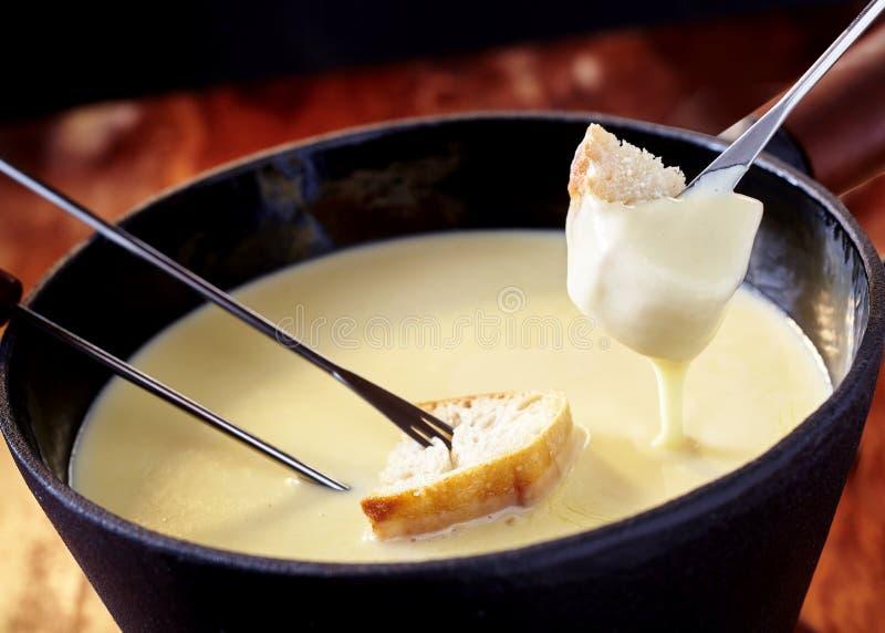 Feche acima em um potenciômetro do fondue de queijo delicioso foto de stock royalty free