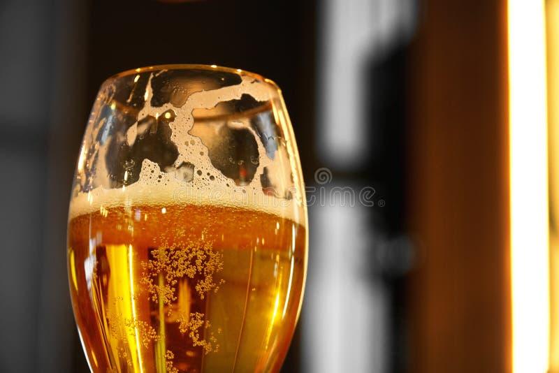 Feche acima em um vidro da pinta da cerveja ambarina de Pale Ale, moldando uma sombra em uma tabela de madeira, e o espaço para o imagens de stock