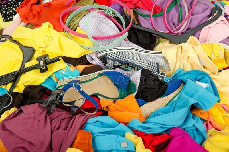 Feche acima em uma pilha grande da roupa e dos acessórios jogados na terra fotos de stock