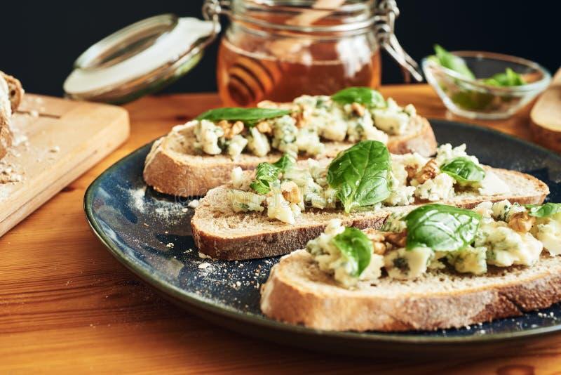 Feche acima em uma placa dos brindes com queijo, nozes, mel e manjericão do roquefort Foco seletivo imagens de stock