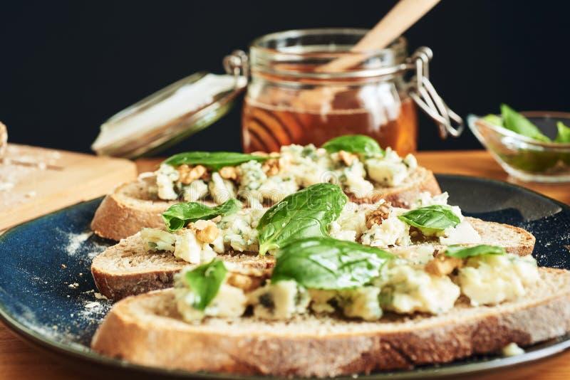 Feche acima em uma placa dos brindes com queijo, nozes, mel e manjericão do roquefort Um frasco do mel no fundo fotografia de stock