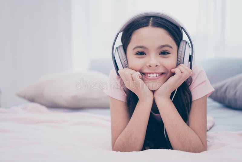 Feche acima a foto bonita ela que sua menina que se encontra para baixo earflaps da cama aprecie ondulado encaracolado da manhã p imagens de stock