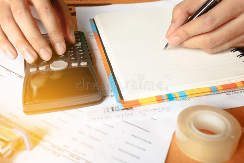Feche acima, homem de negócio ou contador do advogado que trabalham em contas usando uma calculadora e escrevendo em originais fotos de stock royalty free